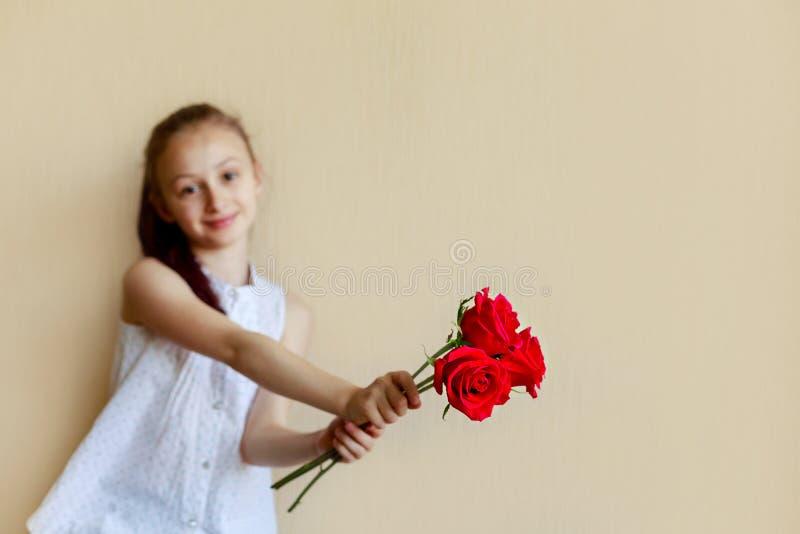 Mały powabny uczennic pereds bukiet czerwoni kwiaty na be?owym tle obraz royalty free