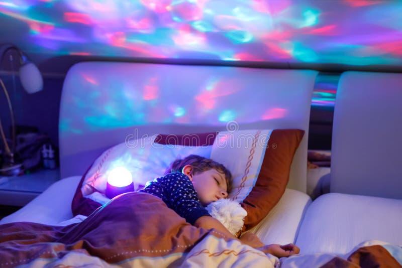 Mały preschool dzieciaka chłopiec dosypianie w łóżku z kolorową lampą zdjęcie stock