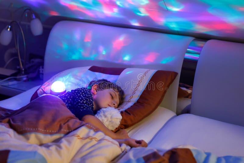Mały preschool dzieciaka chłopiec dosypianie w łóżku z kolorową lampą obraz stock
