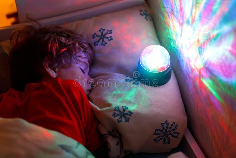 Mały preschool dzieciaka chłopiec dosypianie w łóżku z kolorową lampą fotografia royalty free
