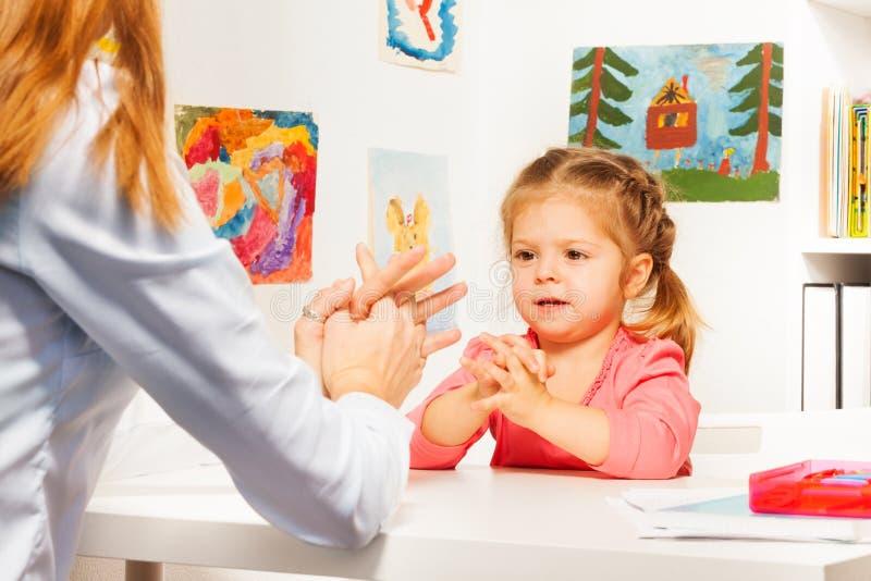 Mały preschooler z jej nauczycielem przy stołem fotografia royalty free