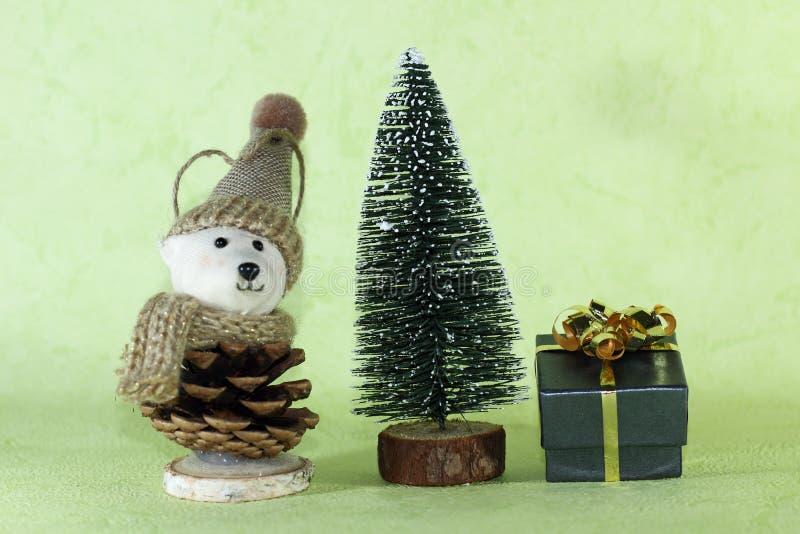 Mały prezent i zabawkarski niedźwiedź z kapeluszem obok dekoracyjni chrismas drzewni na zielonym tle fotografia royalty free