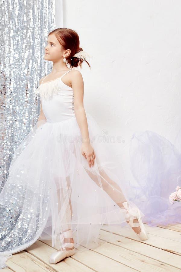 Mały prima balet Młoda baleriny dziewczyna przygotowywa dla baletniczego występu Dziewczyna w balowej todze białym Pointe i obraz royalty free