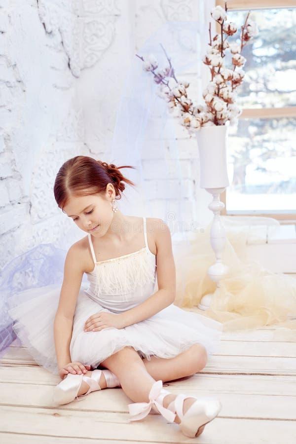 Mały prima balet Młoda baleriny dziewczyna przygotowywa dla baletniczego występu Dziewczyna w balowej todze białym Pointe i fotografia royalty free