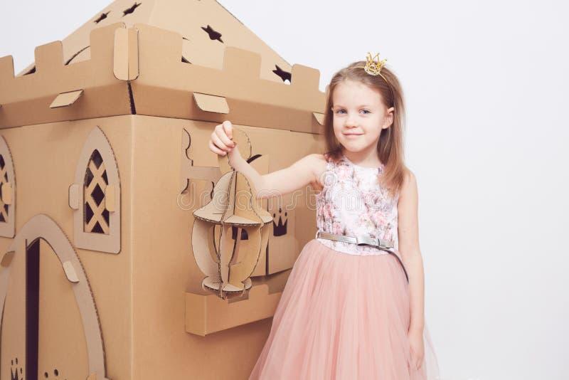 Mały princess w korony sztuce z jej kartonowym kasztelem Prawdziwa emocja szczęście dziecko fotografia stock