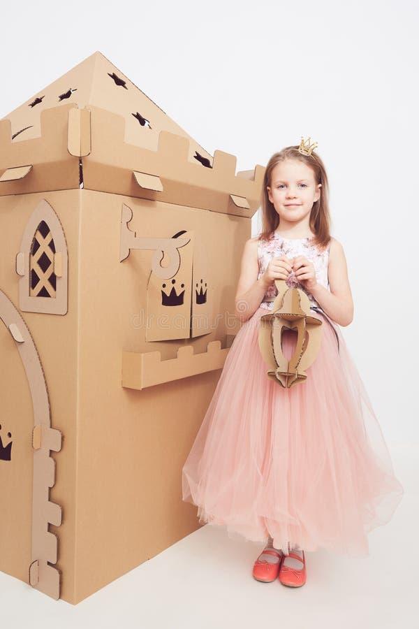 Mały princess w korony sztuce z jej kartonowym kasztelem Prawdziwa emocja szczęście dziecko zdjęcie royalty free