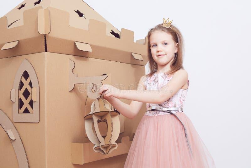 Mały princess w korony sztuce z jej kartonowym kasztelem Prawdziwa emocja szczęście dziecko obraz royalty free