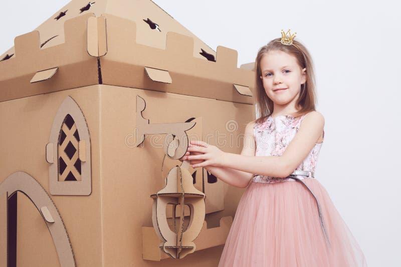Mały princess w korony sztuce z jej kartonowym kasztelem Prawdziwa emocja szczęście dziecko zdjęcie stock