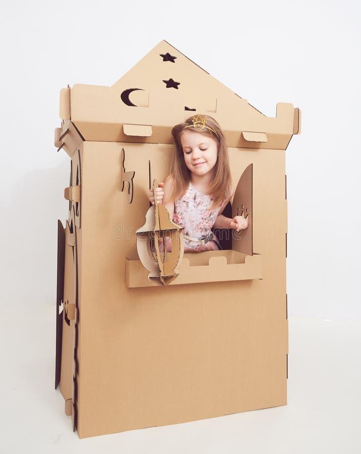 Mały princess w korony sztuce z jej kartonowym kasztelem Prawdziwa emocja szczęście dziecko obrazy royalty free