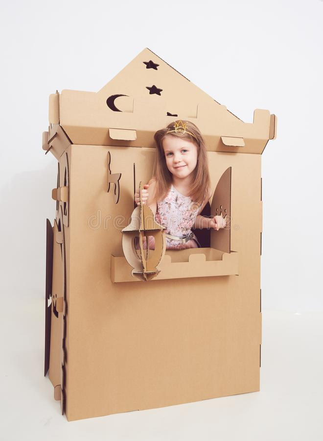 Mały princess w korony sztuce z jej kartonowym kasztelem Prawdziwa emocja szczęście dziecko obraz stock