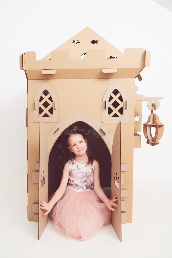 Mały princess w korony sztuce z jej kartonowym kasztelem Prawdziwa emocja szczęście dziecko obrazy stock