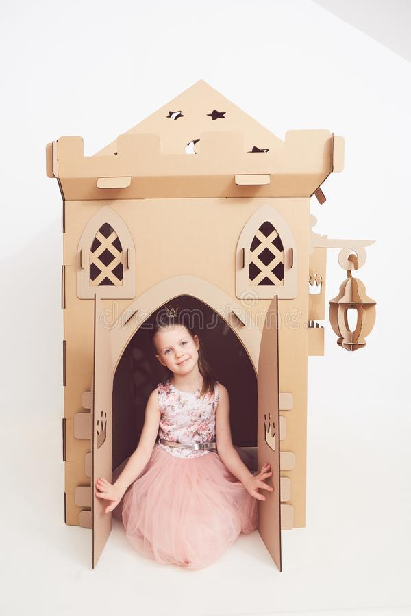 Mały princess w korony sztuce z jej kartonowym kasztelem Prawdziwa emocja szczęście dziecko fotografia royalty free