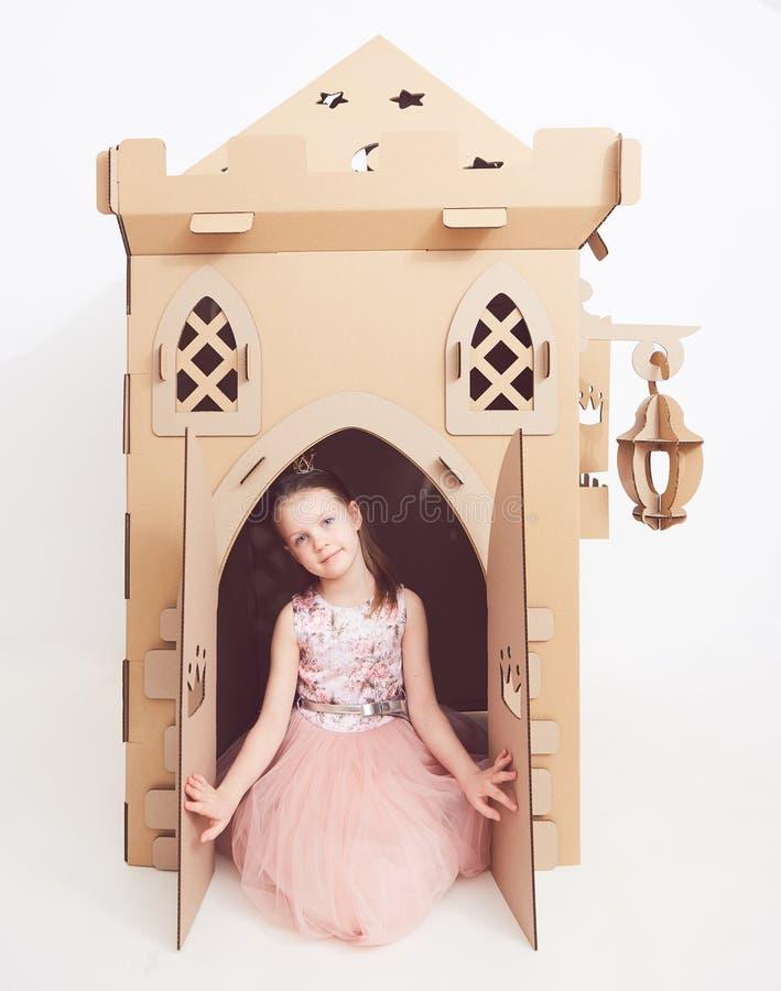 Mały princess w korony sztuce z jej kartonowym kasztelem Prawdziwa emocja szczęście dziecko zdjęcia royalty free