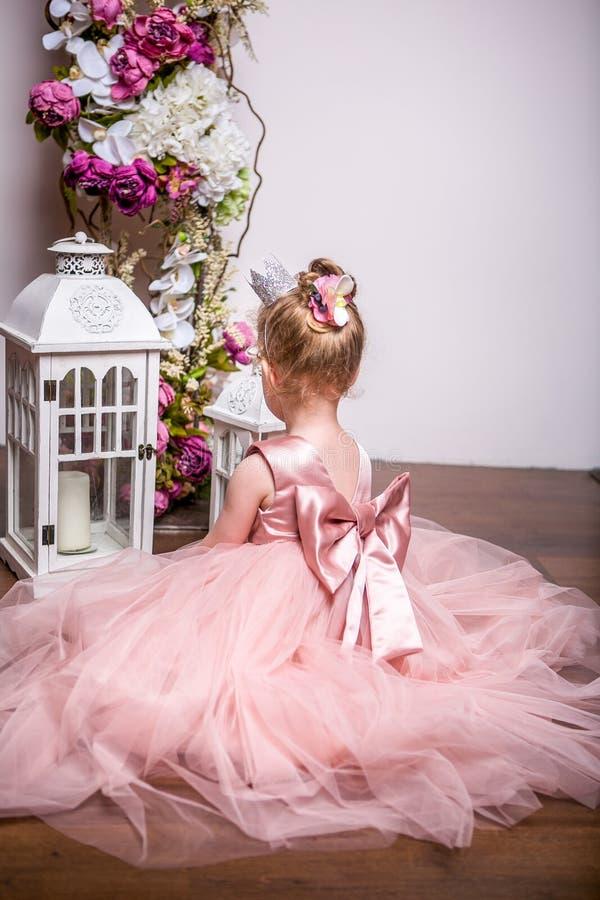 Mały princess w pięknej menchii sukni siedzi na podłoga blisko kwiatu stojaka i otwiera lampion, widok od plecy obraz stock
