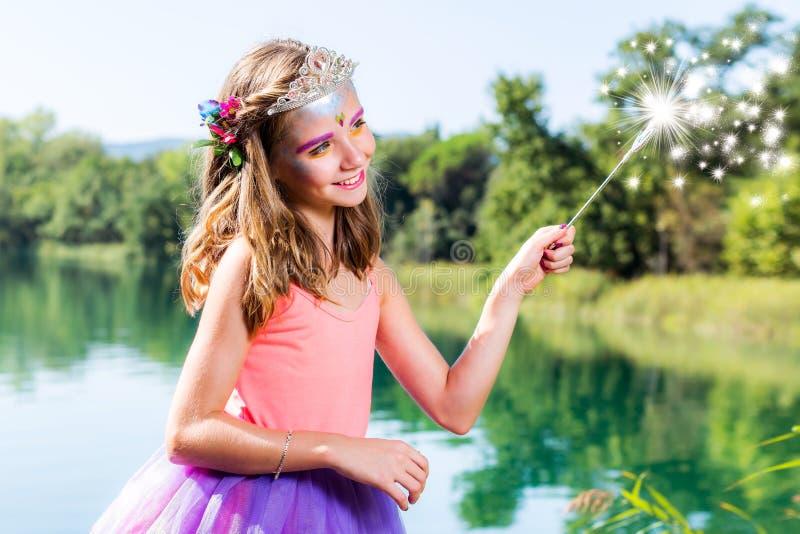 Mały princess z magiczną różdżką przy jeziorem zdjęcie stock