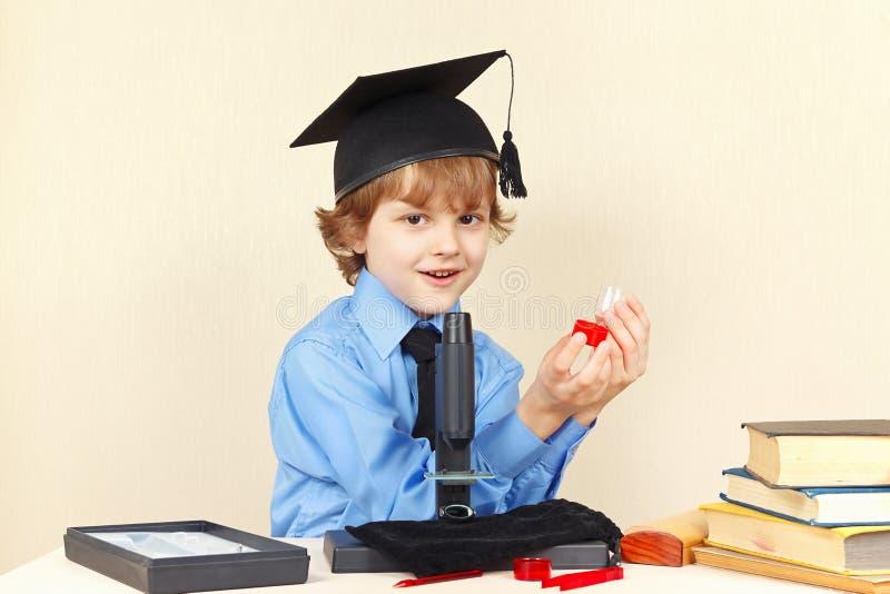 Mały profesor w akademickim kapeluszu z słojami dla badania obok mikroskopu fotografia royalty free