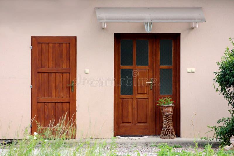 Mały przedmieścia dom rodzinny nowy rustykalne drzwi wejściowe z kwiatowym dzbankiem i czerwonymi kwiatami pokryte przezroczystym zdjęcia royalty free