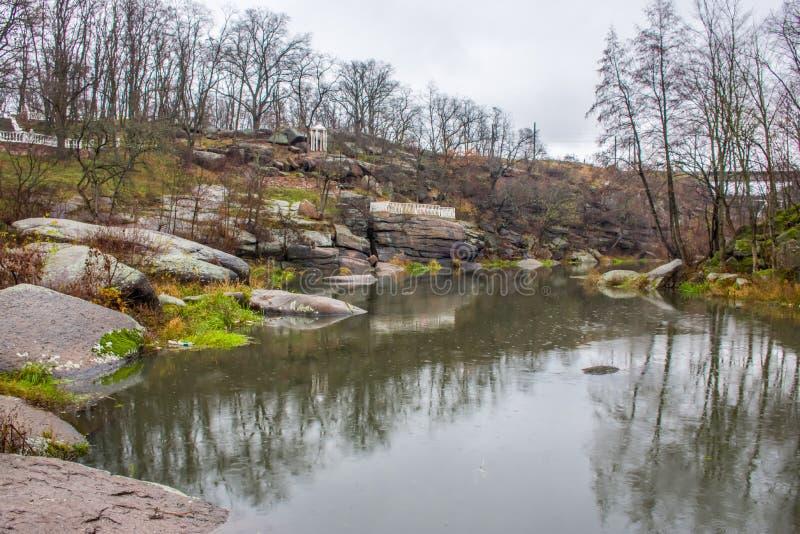 Mały rzeczny unosić się na kamiennym jarze wśród granitowych skał i parku na tle jesień krajobraz z drzewo dowcipem zdjęcia stock