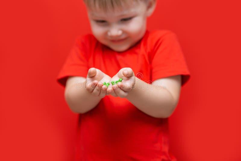 Mały smutny chłopiec dzieciaka chwyt mnóstwo pigułki w rękach czerwona koszulka, czerwonego tła niebezpieczny pojęcie, pastylki i zdjęcia royalty free