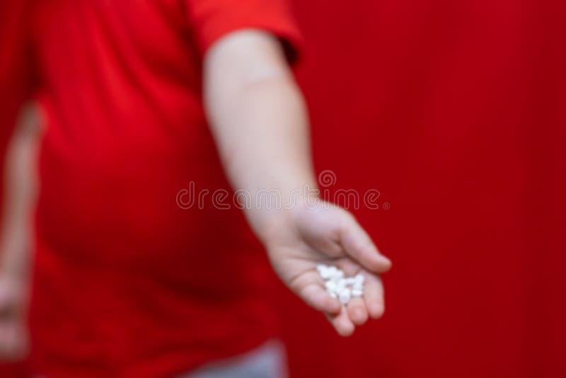 Mały smutny chłopiec dzieciaka chwyt mnóstwo pigułki w rękach czerwona koszulka, czerwonego tła niebezpieczny pojęcie, pastylki i obraz stock