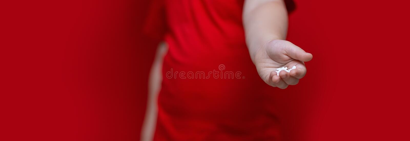 Mały smutny chłopiec dzieciaka chwyt mnóstwo pigułki w rękach czerwona koszulka, czerwonego tła niebezpieczny pojęcie, pastylki i zdjęcia stock