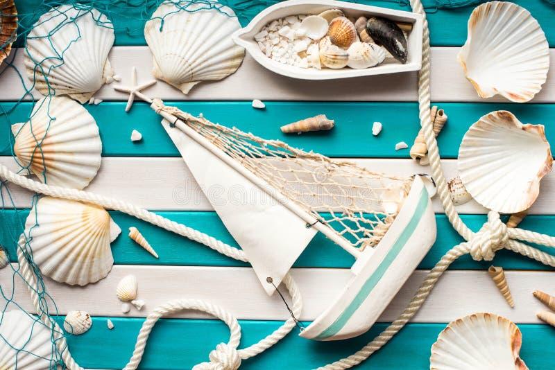 Mały statek, łódź, sieć rybacka, skorupy i żeglarz arkana na drewnianym tle, Denny pojęcie Zasięrzutny widok zdjęcie royalty free