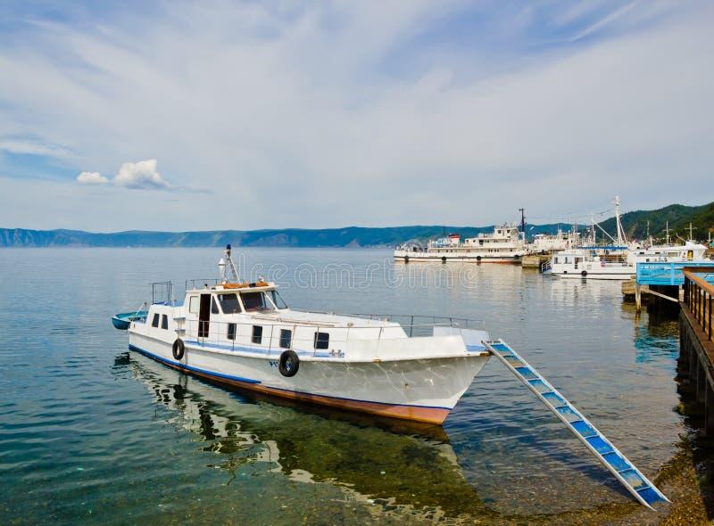 Mały statek przy molem na Jeziornym Baikal w jasnym turkusie nawadnia fotografia stock