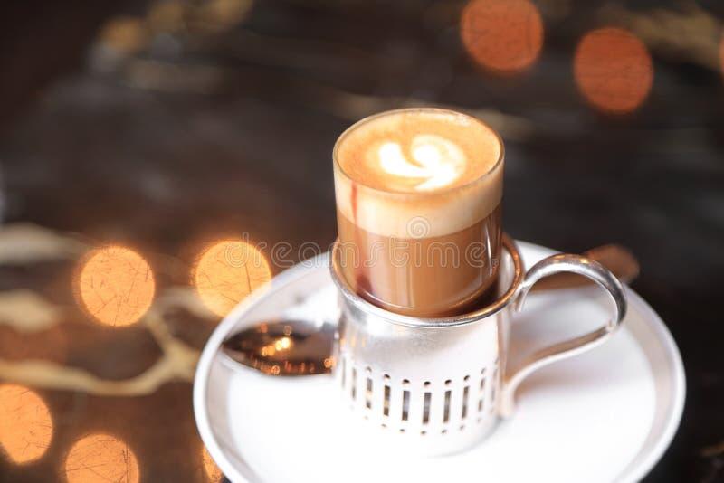 Mały strzał kawa espresso z odparowanym gorącym mlekiem i śmietanką na kawiarnia stole z lekkim bokeh na tle zdjęcie royalty free