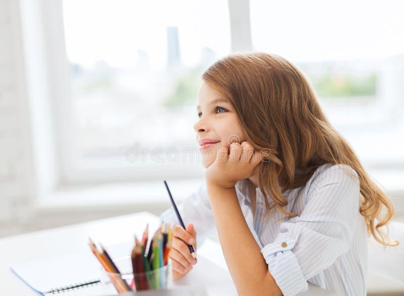 Mały studencki dziewczyna rysunek i marzyć przy szkołą fotografia stock