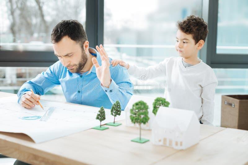 Mały syn rozprasza uwagę jego ojca od pracy zdjęcia royalty free
