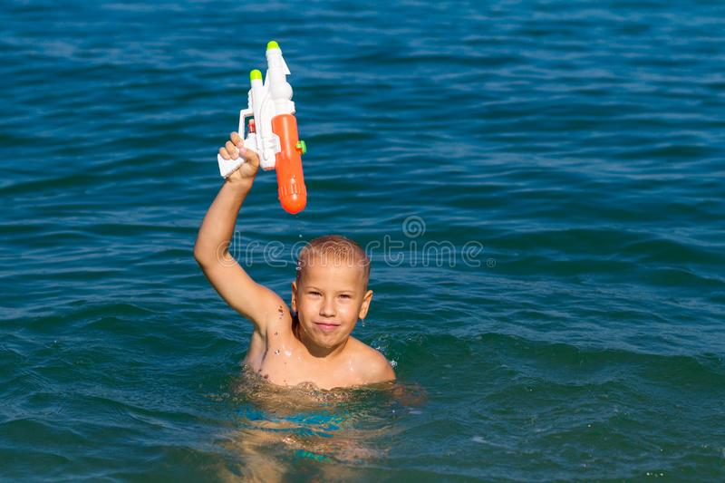 Mały szczęśliwy chłopiec dopłynięcie w morzu z wodnego pistoletu pojęcia szczęśliwym dzieciństwem fotografia stock