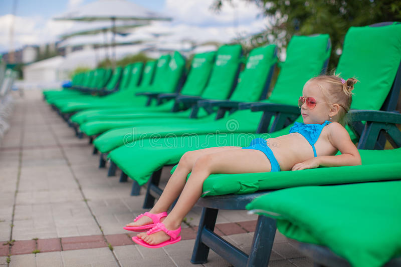 Mały szczęśliwy dziewczyny lying on the beach na loungers obok fotografia stock