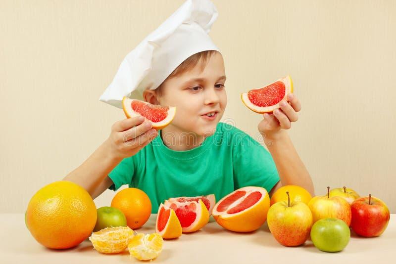 Mały szef kuchni z dwa plasterkami grapefruitowy przy stołem z owoc obraz royalty free