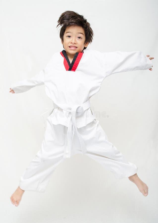 Mały tae kwon robi chłopiec sztuki samoobrony doskakiwaniu zdjęcia stock