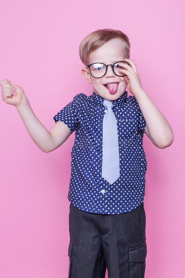Mały uroczy dzieciak w krawacie i szkłach szkoła preschool Moda Pracowniany portret nad różowym tłem fotografia stock