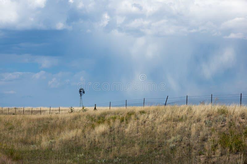 Mały wiatraczek w złotej banatce fied przeciw niebieskiemu niebu z chmurami fotografia stock