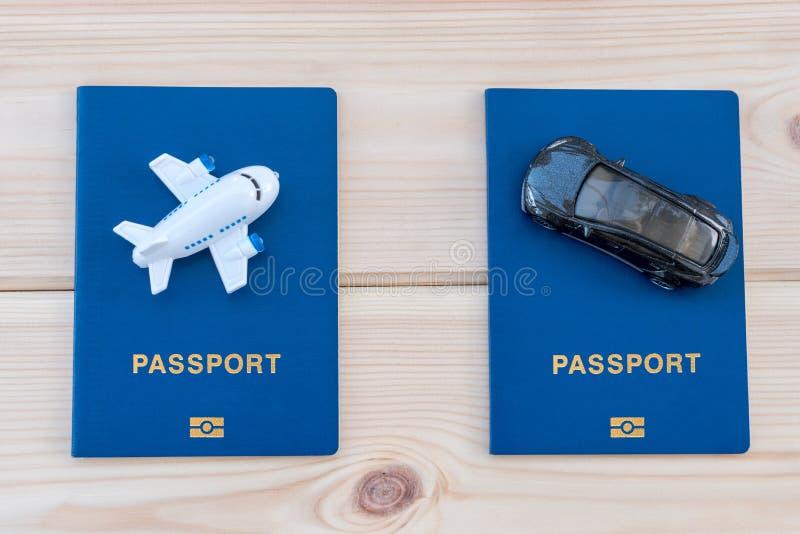 Mały zabawka samolot i zabawka samochód na górze błękitnych paszportów zdjęcie royalty free