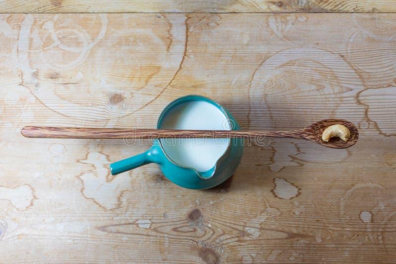 Mały zielony ceramiczny boczny rękojeść pucharu miotacz nerkodrzewu mleko z bardzo tęsk drewniana łyżka i przerzedże nerkodrzewu  zdjęcia stock