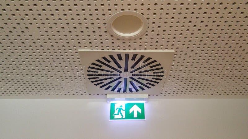 Mały zielony wyjście ewakuacyjne podpisuje wewnątrz biuro fotografia stock