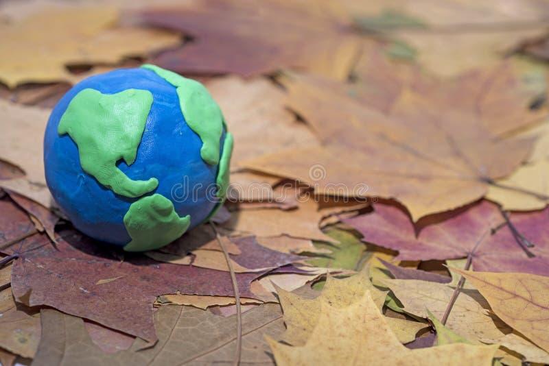 Mały Ziemski model na jesień liści Abstrakcjonistycznym składzie pokój obraz stock