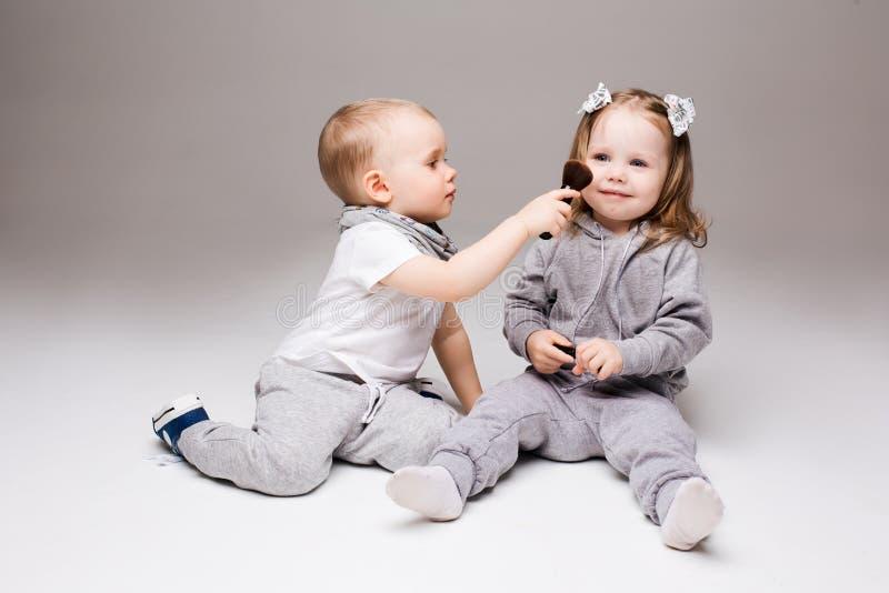 Małych dzieci siedzieć, bawić się przy studiiem z kosmetykami, chłopiec robi makeup dla ładnej blondynki dziewczyny z dwa ogonami fotografia stock
