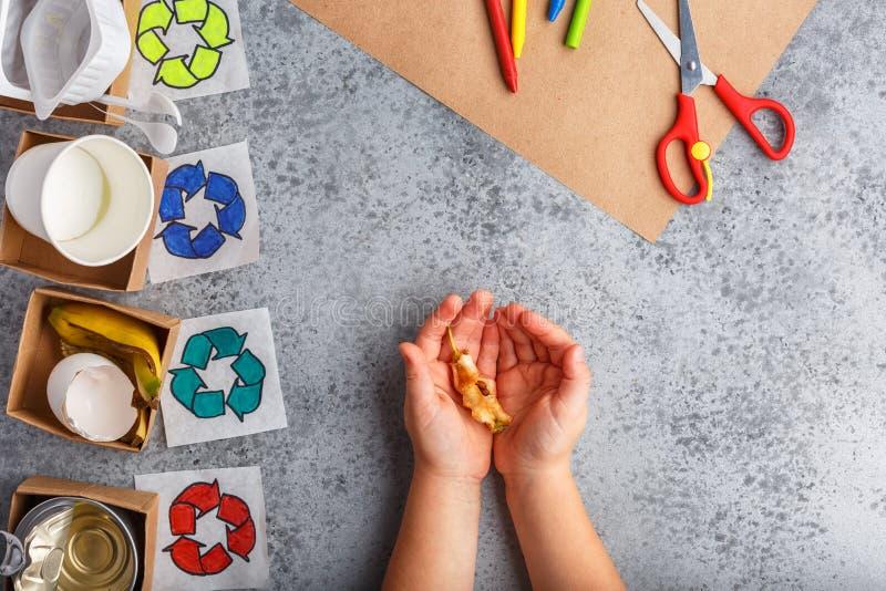 Małych dziewczynek ręki trzymają fiszorek jabłko na popielatym tle przetwarzają pojęcie obraz stock