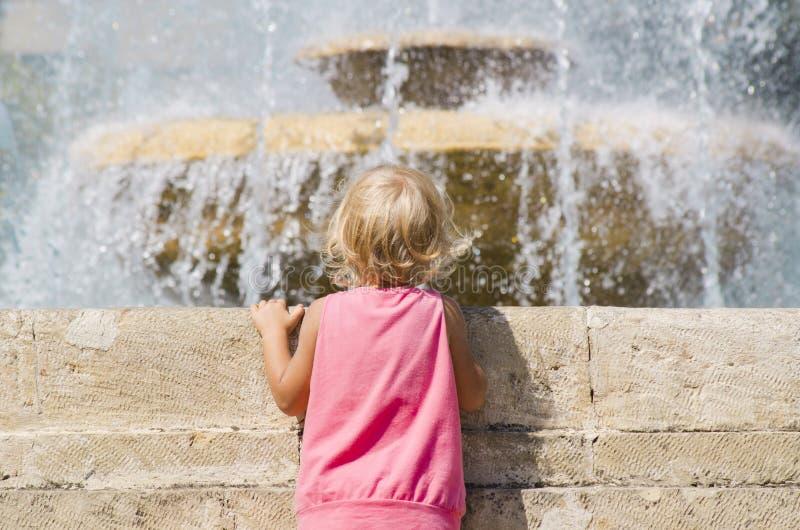 Małych dziewczynek spojrzenia przy fontanną fotografia stock