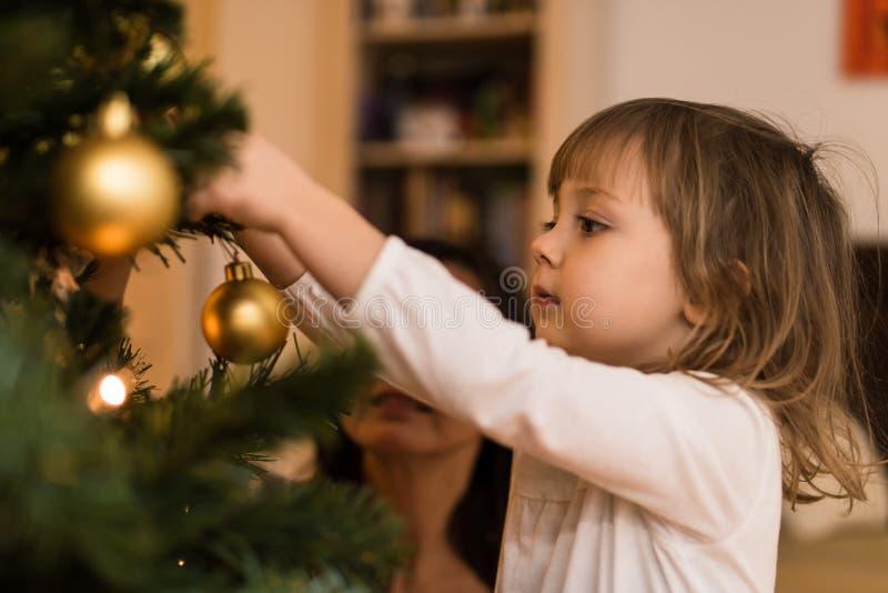Małych dziewczynek wiszący boże narodzenia balowi na drzewie zdjęcia stock