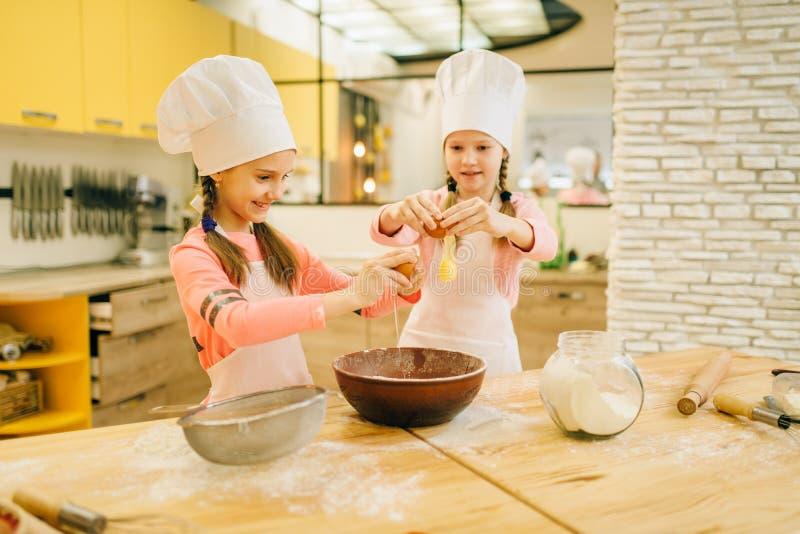 Małych siostr kucharzi w nakrętkach ugniatają jajka w łęku fotografia stock