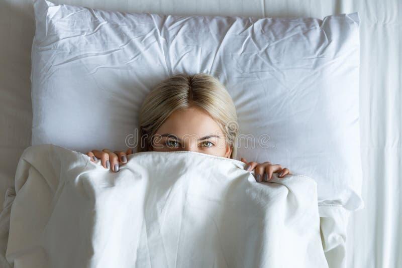Ma?ana feliz Retrato de una mujer rubia joven bonita sonriente que se relaja en la cama blanca fotos de archivo