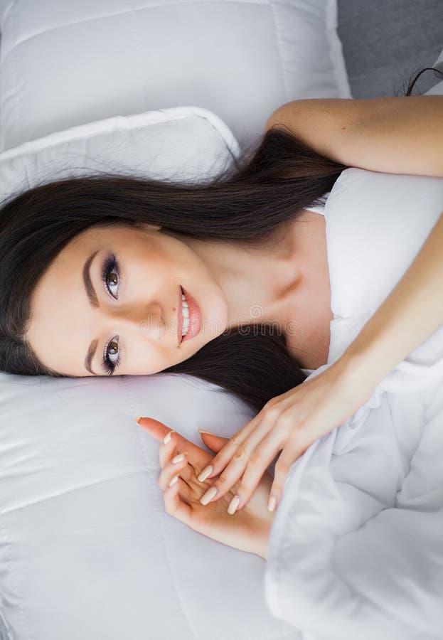 Ma?ana feliz Retrato de una sonrisa mujer morena bastante joven que se relaja en la cama blanca fotografía de archivo