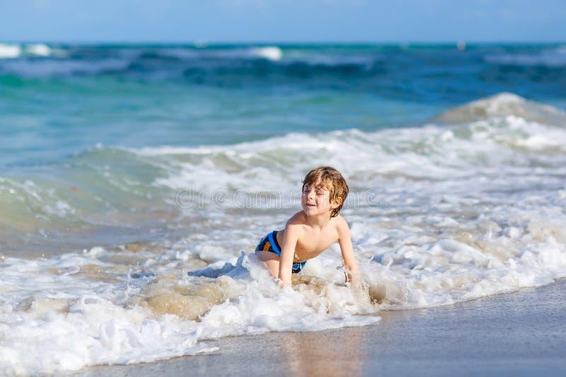 Ma?a blondynu dzieciaka ch?opiec ma zabaw? na ocean pla?y w Floryda zdjęcie royalty free