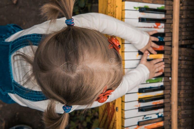 Ma?a dziewczynka bawi? si? koloru pianino Children& x27; s r?ki - na pianinie obrazy stock