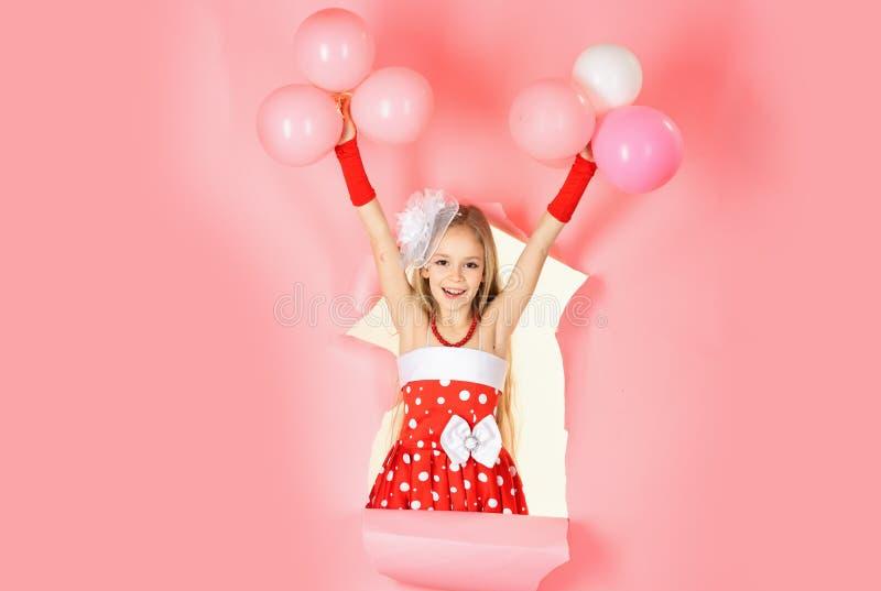 Ma?a dziewczynka bawi? si? z balonami na r??owym tle zdjęcia royalty free